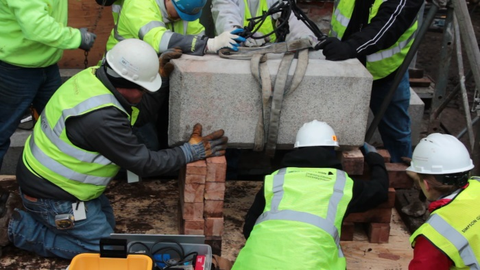 Workers move the State House cornerstone before at...