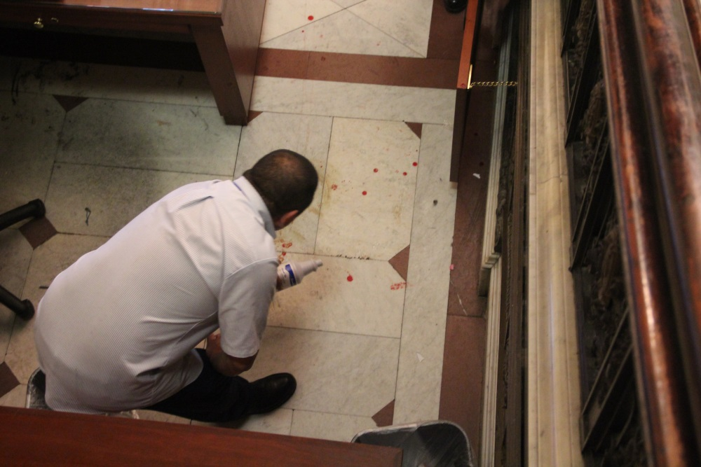 A State House worker cleans blood from behind the